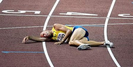 26. TRACK & FIELD - Erik Sjoqvist is exhausted at the finish line of the 5000m event.