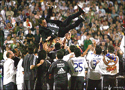 Real Madrid players celebrate their first league title since 2003 by throwing their coach, Capello, in the air