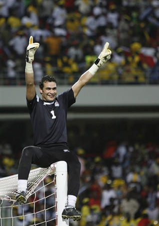 Egypt's goalie Essam Al Hadari celebrates atop the goal post after they beat Cameroon in the African Nations Cup soccer final in Accra February 10, 2008.