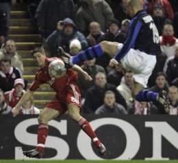 Esteban Cambiasso tries to block a Steven Gerrard cross