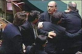 Far-right National Alliance member Domenico Gramazio has to be restrained in the Italian parlament, after coming to blows with Massimo Mauro, a deputy of the ruling Democrats of the Left and a former player with Juventus