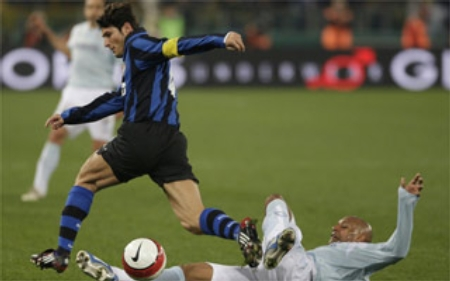Ousmane Dabo (right) slide-tackles the ball away from Javier Zanetti