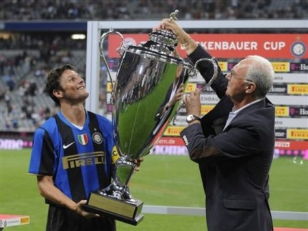 Former German soccer player Franz Beckenbauer, right, presents the trophy to Milan player Javier Zanetti, left, after the soccer friendly match of the Beckenbauer cup between FC Bayern Munich and Inter Milan in the arena in Munich, southern Germany, on Tuesday, Aug. 5, 2008. Milan won the match 1-0 (AP Photo by CHRISTOF STACHE)