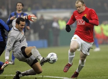 Inter Milan Brazilian goalkeeper Julio Cesar, left, kicks the ball away from Manchester United forward Wayne Rooney during the Champions League soccer match between Inter Milan and Manchester United at the San Siro stadium in Milan, Italy, Tuesday, Feb 24, 2009. (AP Photo)