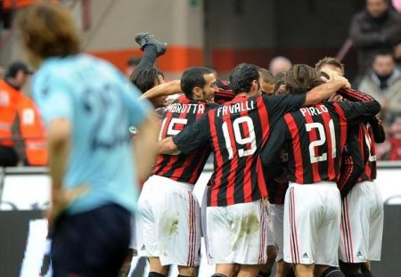 Milan players celebrate their goal against Cagliari as Rossoblu goalkeeper Federico Marchetti (front) looks on