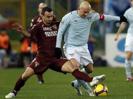 Torino defender Marco Pisano, left, competes for the ball with Lazio forward Tommaso Rocchi during the Serie A soccer match between Lazio and Torino in Rome's Olympic stadium, Saturday, Feb. 14, 2009. (AP Photo by ANDREW MEDICHINI)