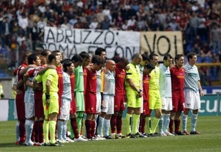 """AS Roma and Lazio players observe a minute of silence to honor the victims of the earthquake that struck the Abruzzo region on Monday, April 6, prior to the start of their Serie A soccer match at Rome's Olympic stadium, Saturday, April 11, 2009. The banner in background reads """"Abruzzo, Rome is with you"""". A 6.3-magnitude quake killed at least 290 people on Monday in the city of L'Aquila and 26 surrounding villages. (AP Photo)"""