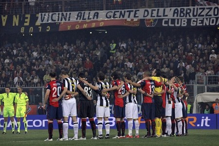 "Football players of Juventus (R) and Genoa observe a minute of silence to pay tribute to the April 6 earthquake's victims prior their serie A football match, at Luigi Ferraris stadium on April 9, 2009 in Genova. The banner displayed in the grandstand reads ""Close to people from Abruzzo region"", where the earthquake killed more than 250 people. (GETTY IMAGES)"